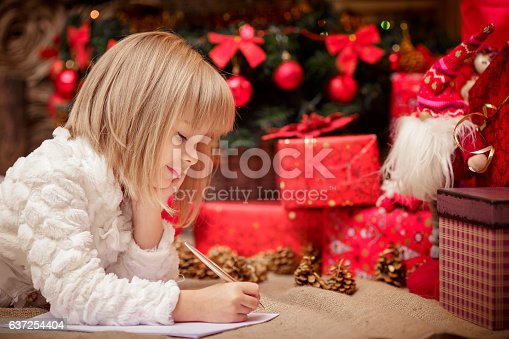 1062609644istockphoto little girl writes a letter to Santa Claus 637254404