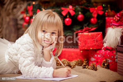 1062609644istockphoto little girl writes a letter to Santa Claus 637254632