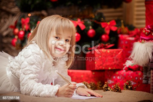 1062609644istockphoto little girl writes a letter to Santa Claus 637255138