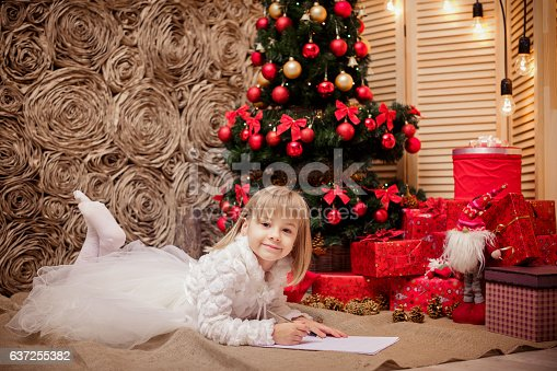 1062609644istockphoto little girl writes a letter to Santa Claus 637255382