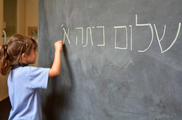 little girl writes hello first grade greetings in hebrew - pismo hebrajskie zdjęcia i obrazy z banku zdjęć