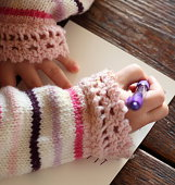 Little girl's hands writing a note with a pen. Right handed.
