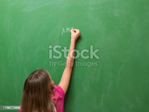 istock Little girl writing abc on blank blackboard 176622688