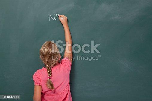 istock Little girl writing abc on blank blackboard 184399184