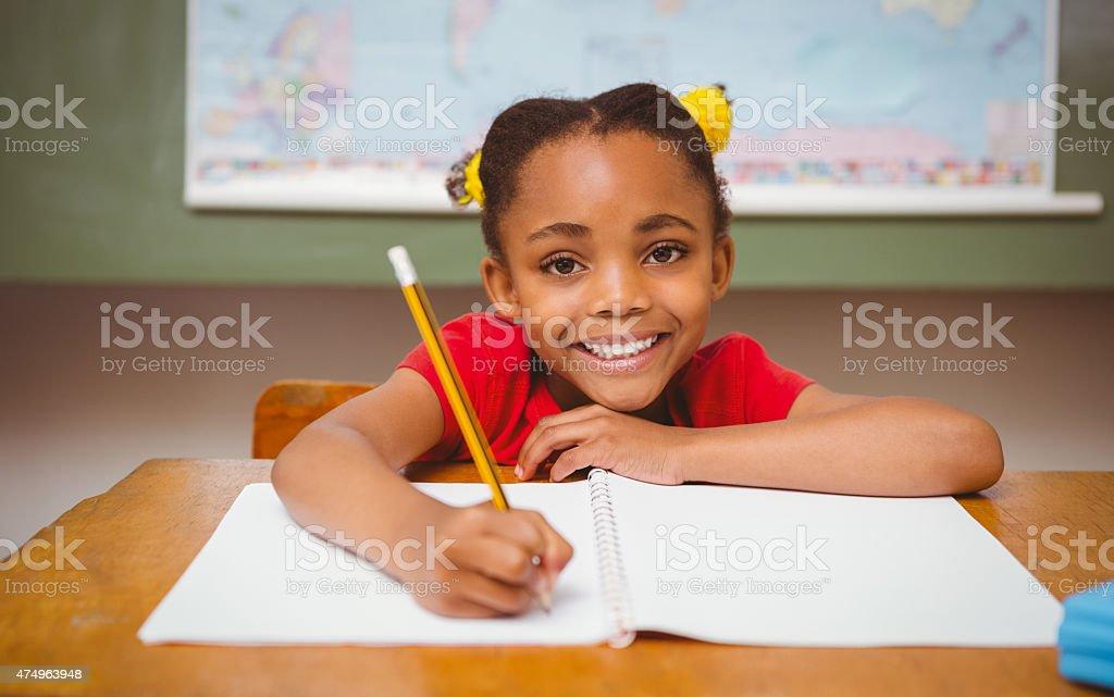 Little girl writing book in classroom stock photo