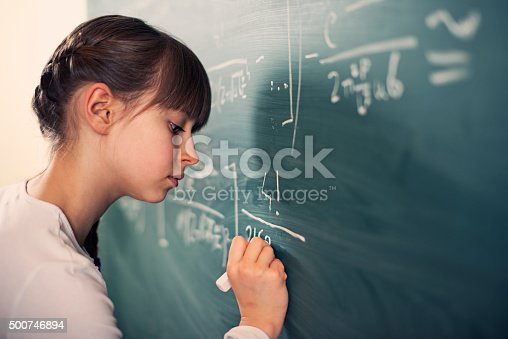 Little mathematics genius girl writing difficult mathematics equations on a green chalkboard. The gilr is smiling focused on solving the equation.