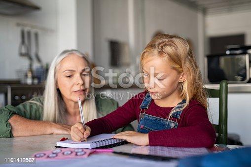 istock Little girl writing in homework notebook 1161412567