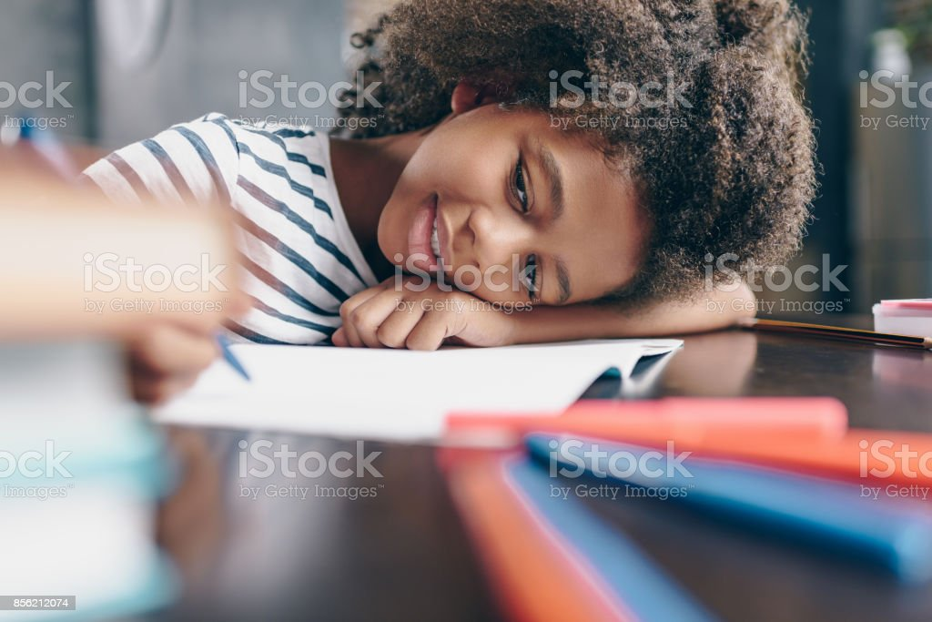 Little girl writing in notebook stock photo