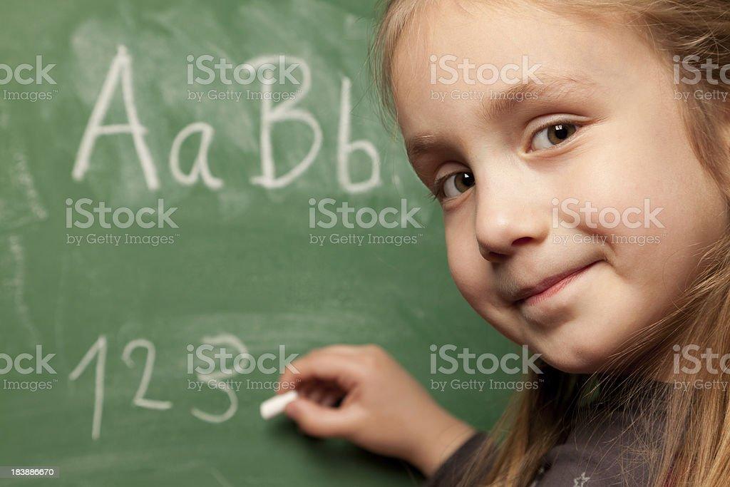 Little girl writing on chalkboard royalty-free stock photo