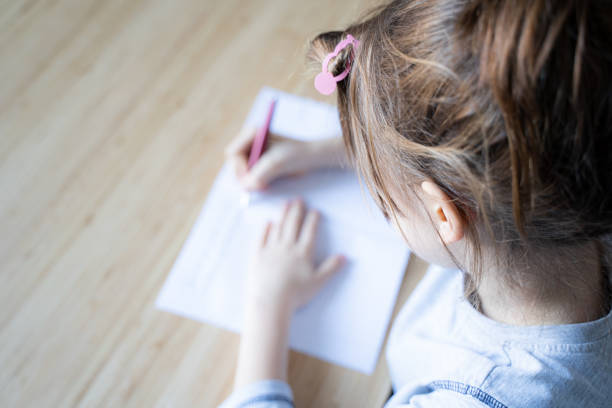 little girl writing with fountain pen in her notebook stock photo