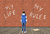 istock Little girl wrote with a chalk on a high brick wall text My Life My Rules 1037284096