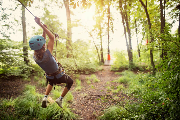 Little girl ziplining in forest Teenage girl wearing a helmet zipping on a line in forest. Nikon D810 zip line stock pictures, royalty-free photos & images