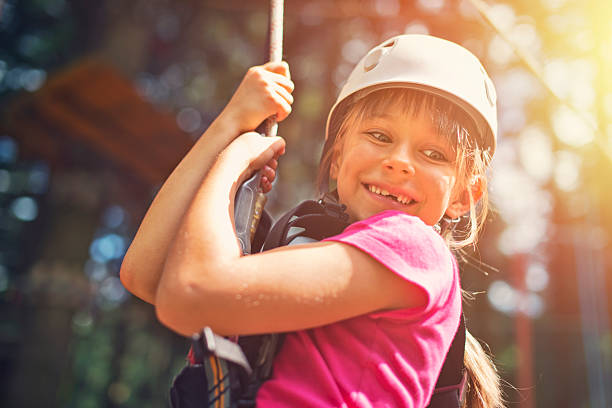 Little girl zipping in zip line adventure park Little girl wearing a helmet, on zip line in adventure park. The girl is aged 7 and is laughing. zip line stock pictures, royalty-free photos & images