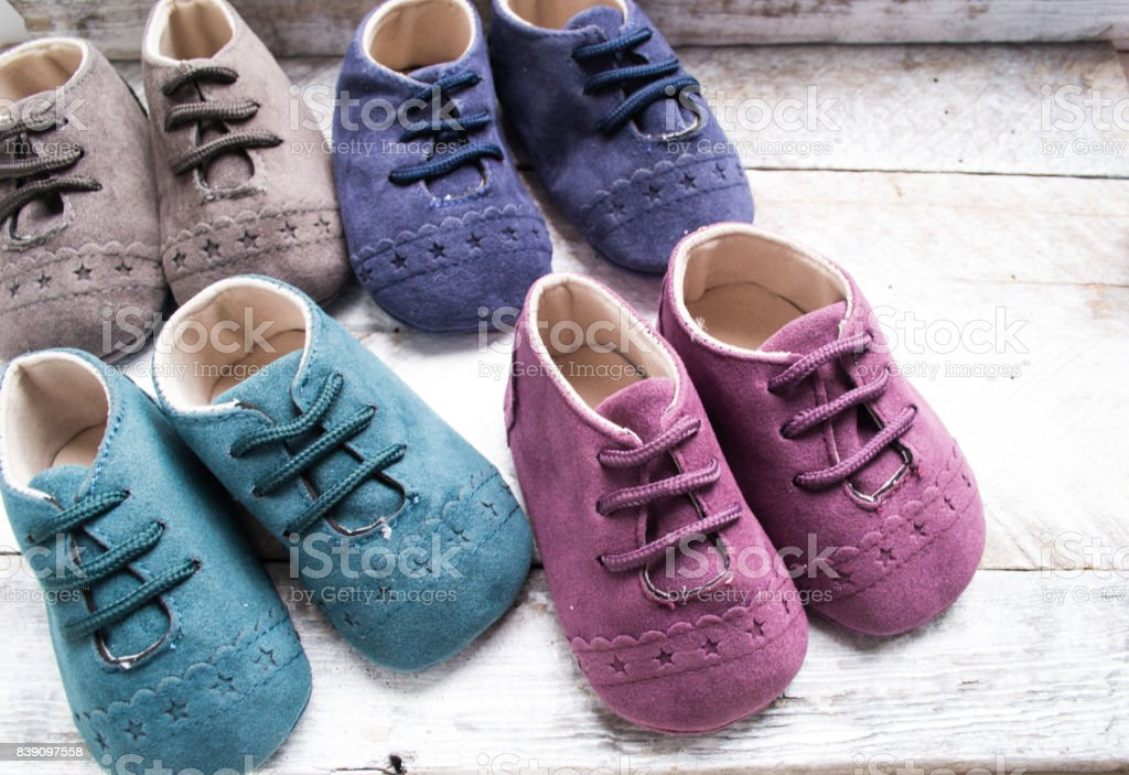 Little girlie baby shoes on a wood stock photo