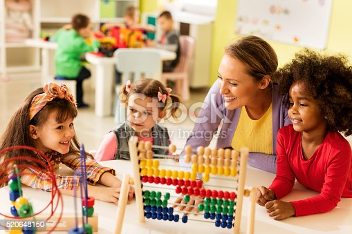 Smiling teacher and little girls talking and playing with educational toys at preschool. Other children are in the background.