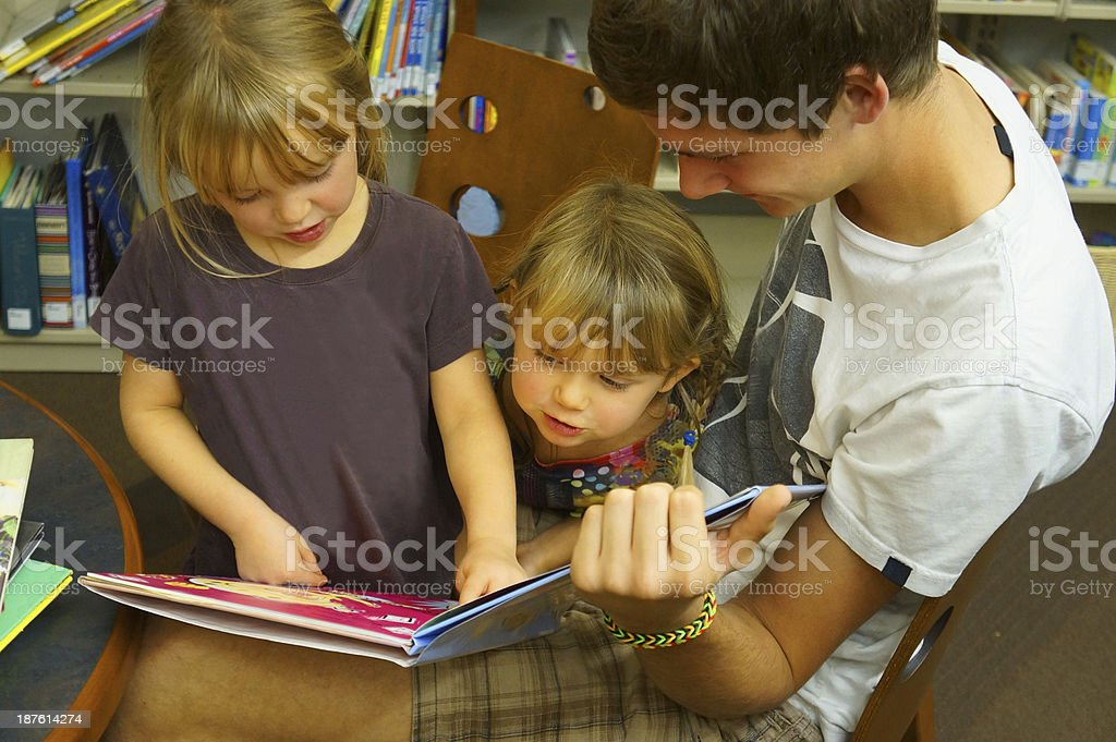 Little girls and teenager in library royalty-free stock photo