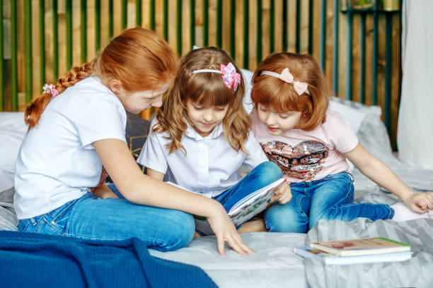 Little girls are considering a book. The concept of lifestyle, c Little girls are considering a book. The concept of lifestyle, childhood, education, family, school. deem stock pictures, royalty-free photos & images