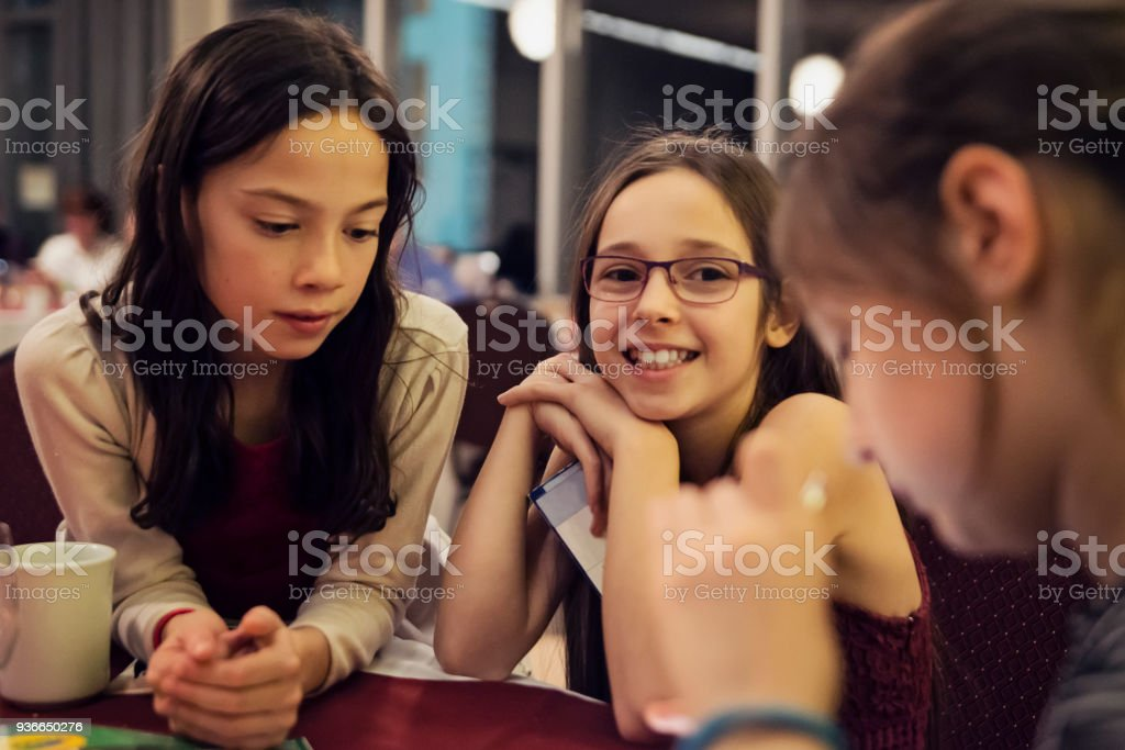 Little Girls At A Table In Big Family Celebration Dinner