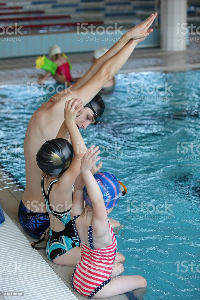 little girls at swimming lesson in indoor swimming pool stock photo