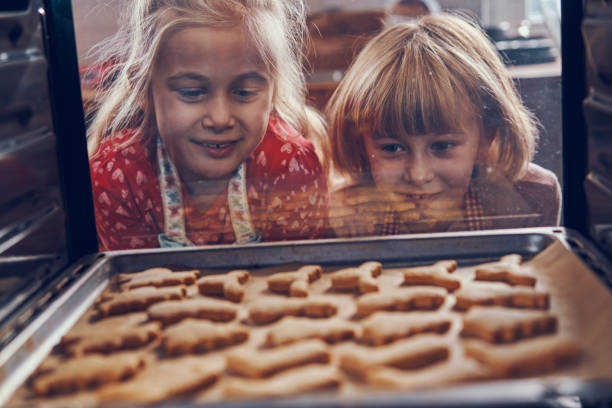 Little Girls Baking Christmas Cookies in the Oven stock photo