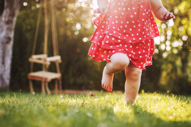 little girl's bare feet in the grass. little girl running  at sunset - scalzo foto e immagini stock