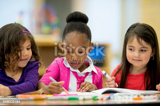 istock Little Girls Coloring Together 546003184