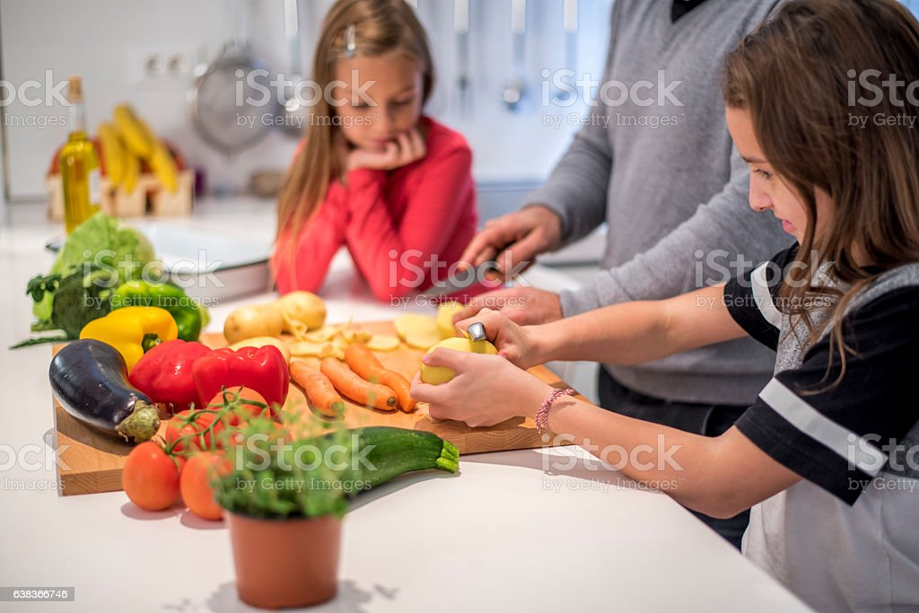 Little girls cooking together with their father stock photo