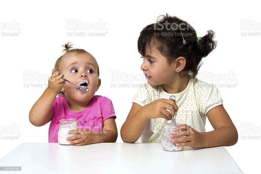 little girls eating yogurt stock photo