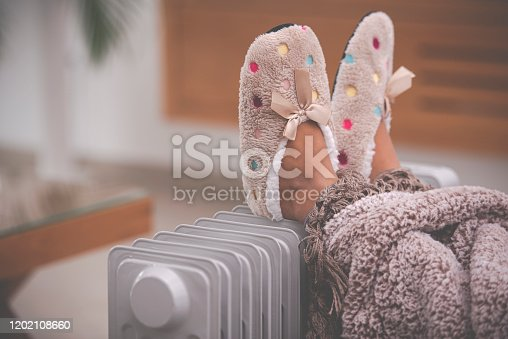 Little girl's feet in slippers with Polka dots and ribbon bow, lying on radiator heater in the living room. Legs covered with a warm blanket. Kid staying at home in the winter season.