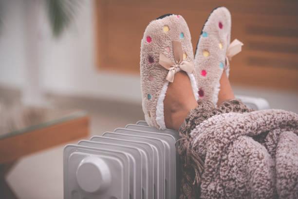 Little girl's feet in slippers on radiator heater. stock photo