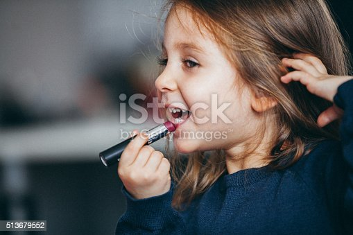 istock Little girl's first lipstick 513679552