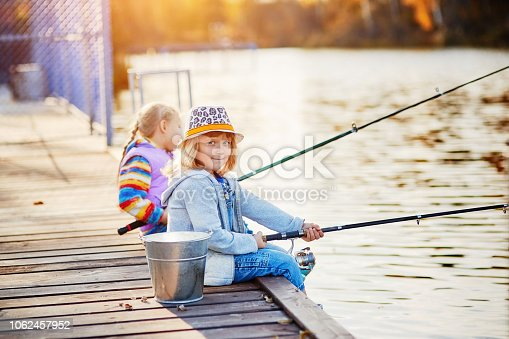 Little girls fishing on the lake, sitting on a wooden pontoon.