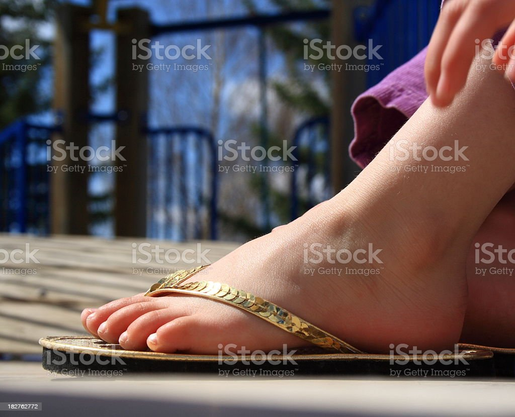 c4a20d474afea1 Little girl s foot wearing shiny gold sequined flip flop sandle  royalty-free stock photo