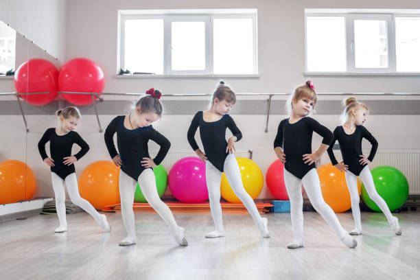 Little girls go dancing in a dance class. The concept of sport, education, childhood, hobbies and dance. Little girls go dancing in a dance class. The concept of sport, education, childhood, hobbies and dance dance studio stock pictures, royalty-free photos & images