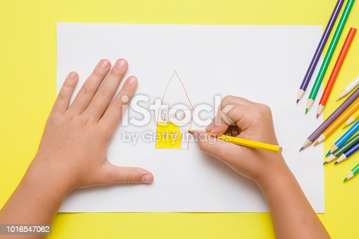 istock Little girl's hand painting house on the white paper with yellow pencil. Color pencils on the desk. Drawing time. Top view. 1016547062