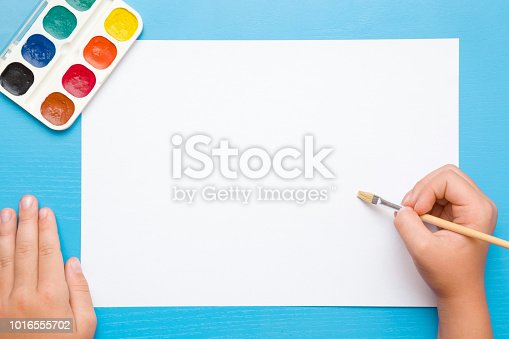 818533812 istock photo Little girl's hand painting on the white paper with paintbrush. Colorful watercolors on the blue desk. Drawing time. Top view. Empty place. 1016555702