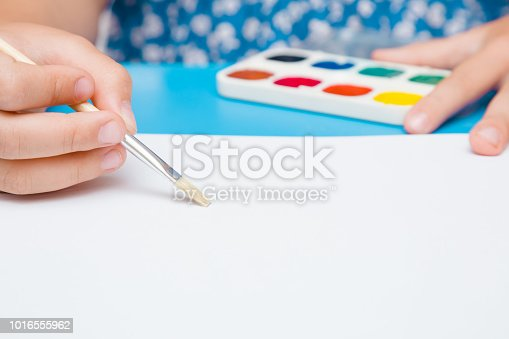 818533812 istock photo Little girl's hand painting on the white paper with paintbrush. Colorful watercolors on the blue desk. Drawing time. Front view. Close up. Empty place. 1016555962