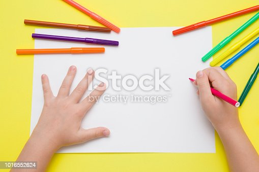 818533812 istock photo Little girl's hand painting on the white paper with pink color pen. Colorful markers on the yellow desk. Drawing time. Top view. Empty place. 1016552624