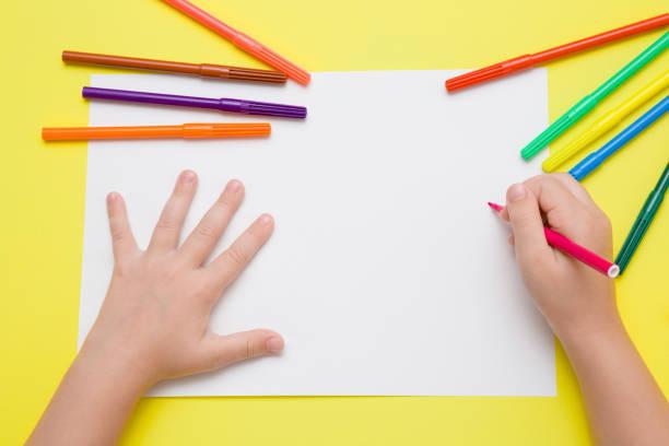 Kleines Mädchen Handmalerei auf weißem Papier mit rosa Farbe Stift. Farbige Markierungen auf dem gelben Schreibtisch. Zeichnung-Zeit. Ansicht von oben. Leeren Platz. – Foto