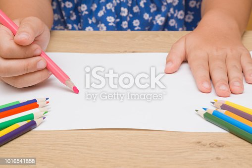 818533812 istock photo Little girl's hand painting on the white paper with pink pencil. Color pencils on the wooden desk. Drawing time. Front view. Close up. Empty place. 1016541858
