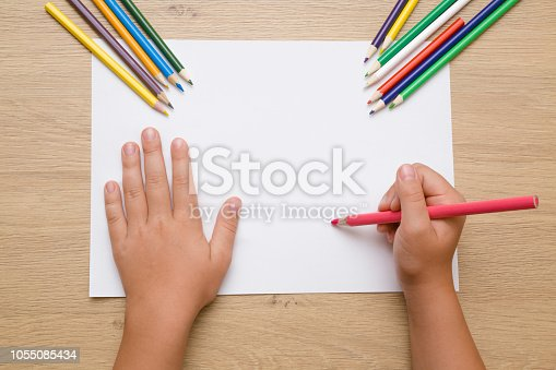 istock Little girl's hand painting on the white paper with pink pencil. Color pencils on the wooden desk. Drawing time. Top view. Empty place. 1055085434