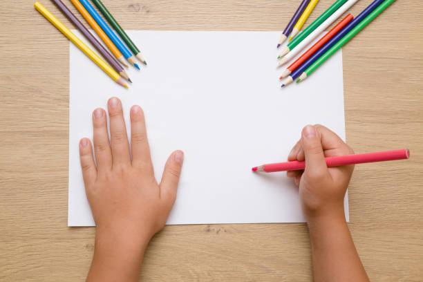 pintura de la mano de la niña sobre el papel blanco con lápiz de color de rosa. lápices de color sobre el escritorio de madera. tiempo de dibujo. vista superior. lugar vacío. - dibujar fotografías e imágenes de stock