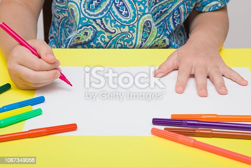 istock Little girl's hand painting on white paper with pink color pen. Colorful markers on yellow desk. Drawing time. Front view. Closeup. 1067349058