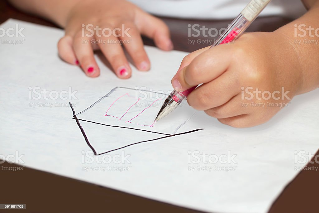 Little girl's hands with ballpen drawing a house stock photo