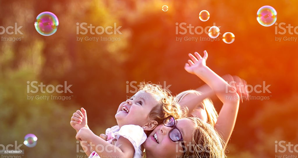 Little girls having bubble fun outdoors stock photo