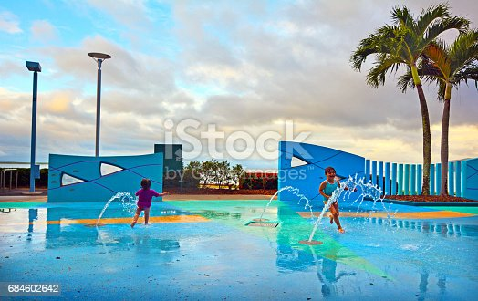 Little sister girls (age 01 and 05) having fun in Cairns Esplanade public water park, a very popular tourist travel destination in Cairns Queensland, Australia.