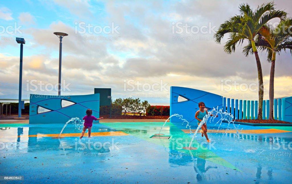 Little girls having fun in Cairns Esplanade public water park in Queensland Australia stock photo