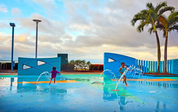 Little girls having fun in Cairns Esplanade public water park in Queensland Australia stock photo