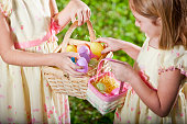 Sisters (6 and 9 years) with Easter baskets, exchanging eggs.  Shallow DOF, focus on eggs in larger basket.