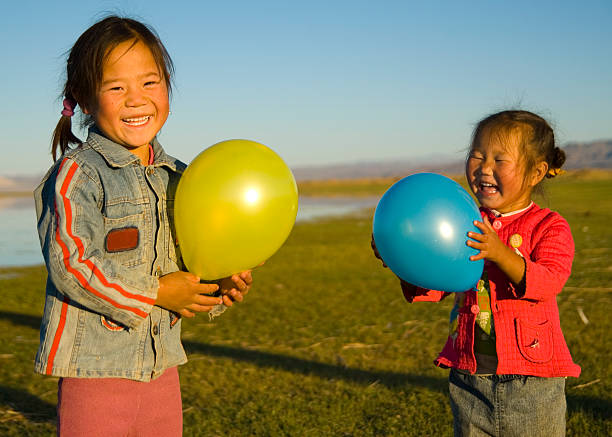 Little girls holing balloons in a field Asian girls playing by a lake. mongolian culture stock pictures, royalty-free photos & images